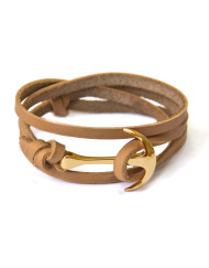 Gold anchor bracelet on beige leather